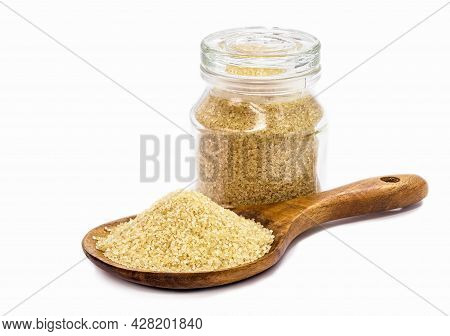 Wooden Spoon With Of Unrefined Raw Cane Sugar Pile, And Glass Jar In The Background, Isolated With B