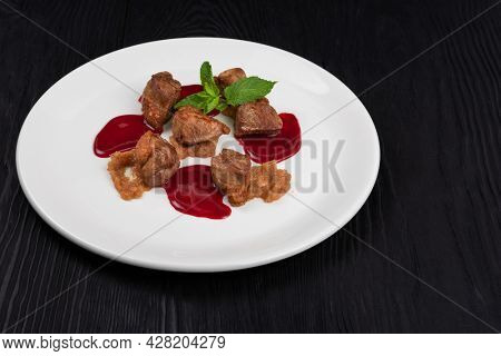 Pork meat with berries sauce and mint on white plate on wooden black background