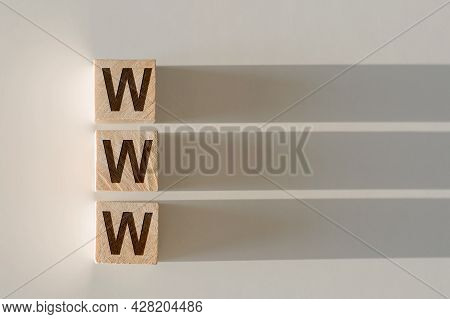 Wooden Cubes With The Word Www, With A Falling Shadow On A Gray Background.
