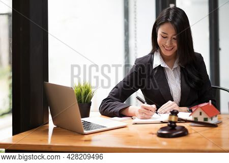 Close Up Business Woman And Lawyers Discussing Contract Papers With Brass Scale On Wooden Desk In Of