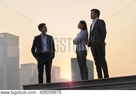 Team Of Asian Corporate Executives Standing On A Platform Chatting Talking Conversing At Dusk With C