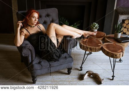 Beautiful Redhead Woman In Black Dress Sitting In Chair Took Off Her Shoes, Concept Of Uncomfortable