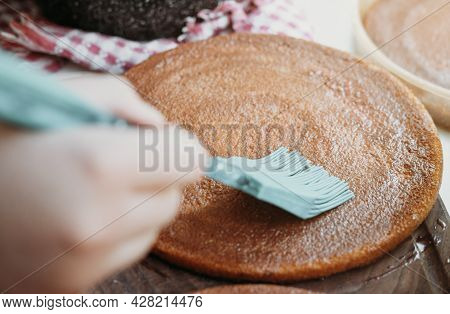 Spreading Berry Sauce On A Cake With Kitchen Brush. Home Baking Concept.