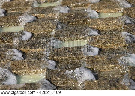 Water Flows Down A Granite Grate, Foam Stream, A Fragment Of A Fountain, Granite, Background