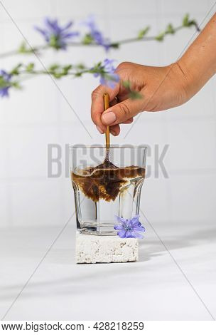 A Womans Hand Will Pour Granulated Chicory Powder Into A White Mug. Drink Chicory.