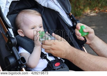 Cute Baby Drinks Water From A Baby Bottle. Water Balance In The Body. Cold Soft Drinks With Fruit. C