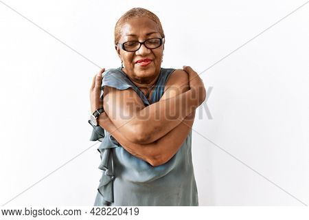 Mature hispanic woman wearing glasses standing over isolated background hugging oneself happy and positive, smiling confident. self love and self care