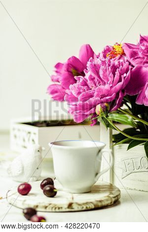 Shabby Chic Tea. A Cup Of Tea On A White Wooden Tray With A Cherry Nearby. Peonies Are In A White Bo