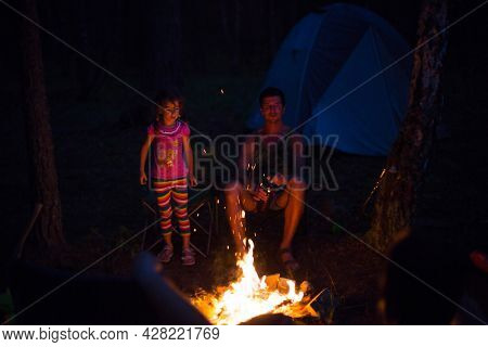Dad And Daughter Sit At Night By The Fire In The Open Air In The Summer In Nature. Family Camping Tr