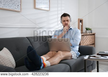 Businessman In Underwear Pretending To Wear Formal Clothes During Video Call At Home