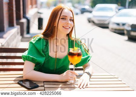 Close-up Portrait Of Happy Smiling Young Woman Drinking Cocktail Through Straw Sitting At Table In O
