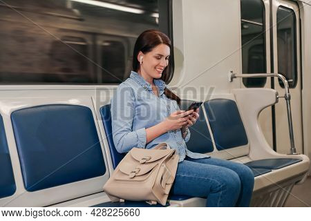 Beautiful Woman With Mobile Phone And Earbuds Listening To Music In Subway Train. Public Transport