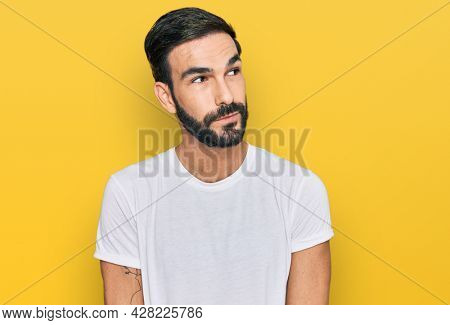 Young hispanic man wearing casual white t shirt smiling looking to the side and staring away thinking.