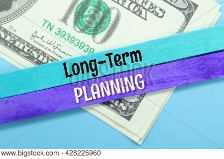 Banknotes, Colored Ice Cream Sticks With The Words Long-term Planning
