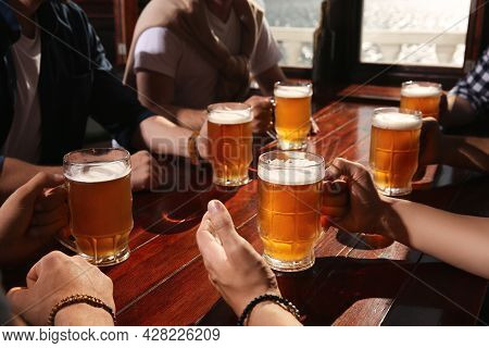Friends With Tasty Beer At Wooden Table In Pub, Closeup