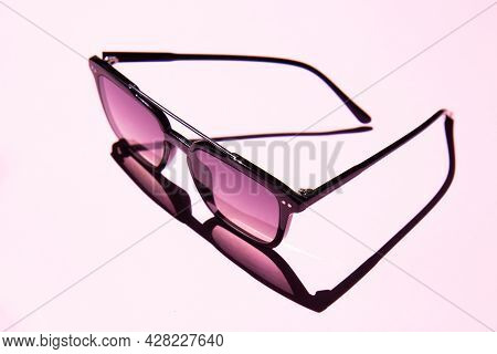 Black Eye Sunglasses Isolated On Pink Background With Contrasting Shadows With Copy Space