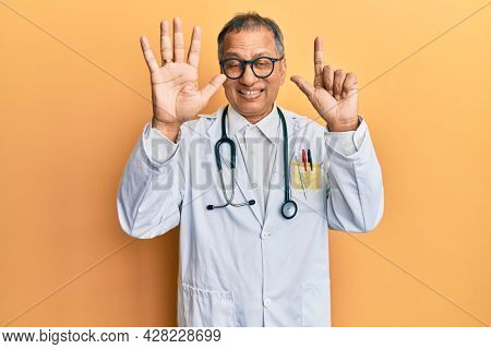 Middle age indian man wearing doctor coat and stethoscope showing and pointing up with fingers number seven while smiling confident and happy.