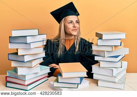 Young caucasian woman wearing graduation ceremony robe sitting on the table smiling looking to the side and staring away thinking.