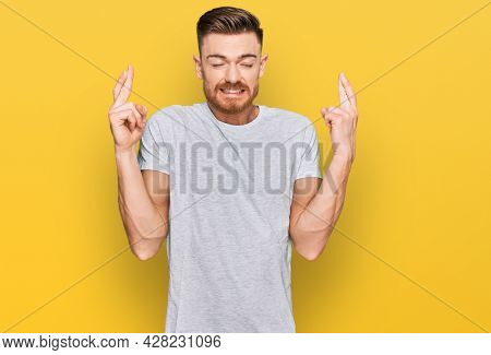 Young redhead man wearing casual grey t shirt gesturing finger crossed smiling with hope and eyes closed. luck and superstitious concept.