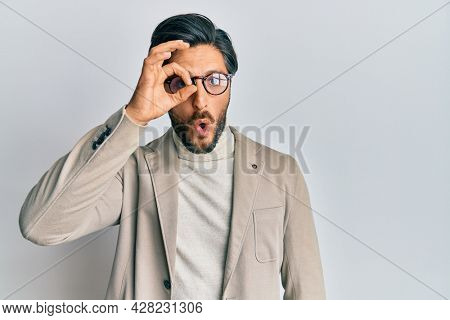 Young hispanic man wearing business jacket and glasses doing ok gesture shocked with surprised face, eye looking through fingers. unbelieving expression.