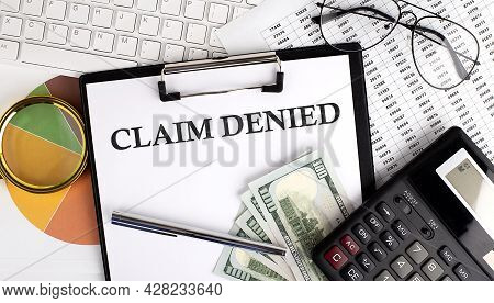 Text Claim Denied On Office Desk Table With Keyboard,dollars,calculator ,supplies,analysis Chart On