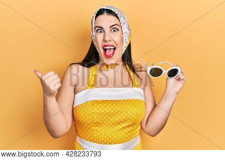 Young hispanic woman wearing pin up style pointing thumb up to the side smiling happy with open mouth