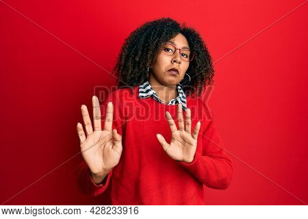 Beautiful african american woman with afro hair wearing sweater and glasses moving away hands palms showing refusal and denial with afraid and disgusting expression. stop and forbidden.