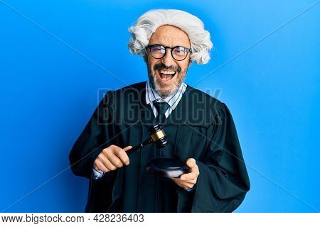 Middle age hispanic man using gavel smiling and laughing hard out loud because funny crazy joke.