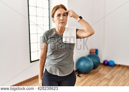 Middle age woman wearing sporty look training at the gym room pointing unhappy to pimple on forehead, ugly infection of blackhead. acne and skin problem