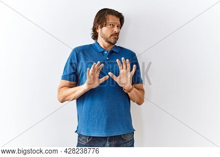 Handsome middle age man standing together over isolated background disgusted expression, displeased and fearful doing disgust face because aversion reaction.