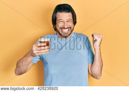Middle age caucasian man drinking a pint of beer screaming proud, celebrating victory and success very excited with raised arm