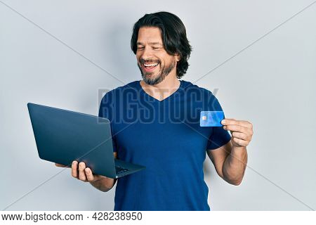 Middle age caucasian man wearing business style holding laptop and credit card smiling and laughing hard out loud because funny crazy joke.