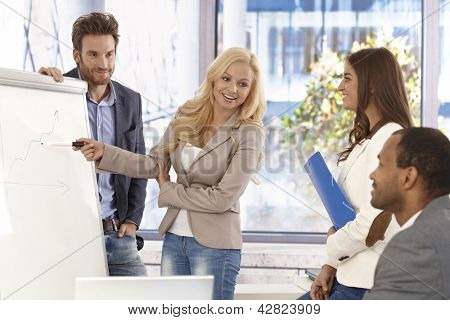 Attractive young businesswoman presenting to colleagues on whiteboard, smiing.