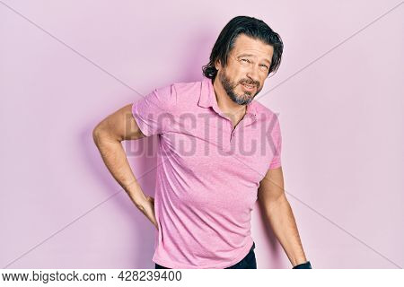 Middle age caucasian man wearing casual white t shirt suffering of backache, touching back with hand, muscular pain
