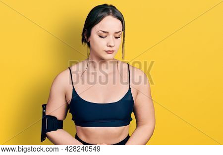 Young hispanic woman wearing sportswear with hand on stomach because indigestion, painful illness feeling unwell. ache concept.