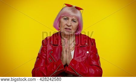 Please, God Help Me. Mature Old Granny Grandmother In Red Jacket Praying, Looking Upward And Making