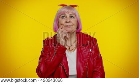 I Need To Think. Thoughtful Clever Senior Rocker Woman Rubbing Her Chin And Looking Aside With Pensi