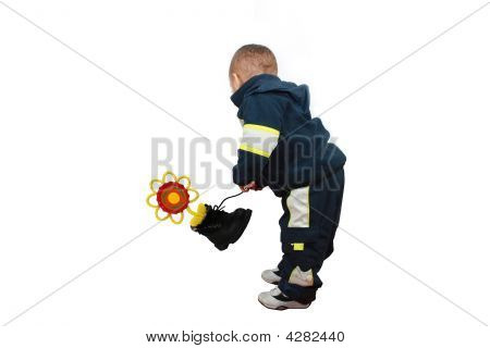 Photograph of a one year old toddler boy holding his boot that has a plastic flower with a recycle emblem. poster