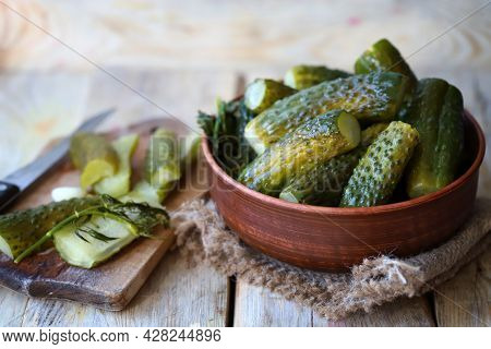 Pickles In A Bowl On A Wooden Surface.