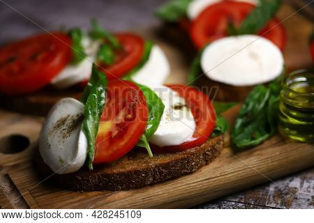 Caprese Toast On A Wooden Board. Italian Mood Dish.
