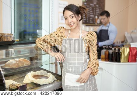 A Beautiful Woman Bakery Or Coffee Shop Owner Is Smiling In Her Shop