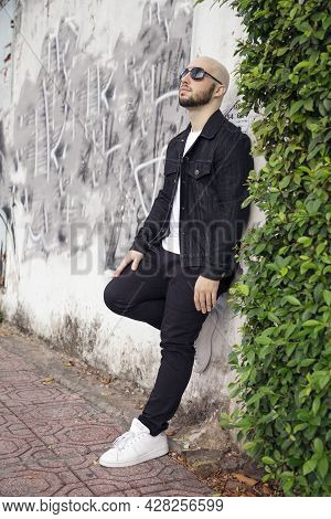 Cool Confident Young Man Wearing Casual Black Clothing And Sunglasses, Leaning On A Wall. Bald Cauca