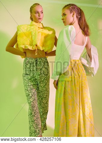 Haute couture fashion. Two fashion models girls pose in stylish clothes from the summer collection. Studio portrait on a light green background. Trendy summer colors in clothes.