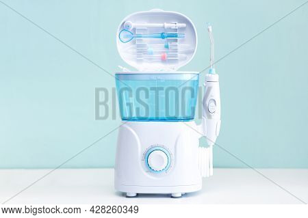 Water Flosser, Dental Oral Irrigator On A Blue Background. Dental Equipment Care. Irrigator For Mout