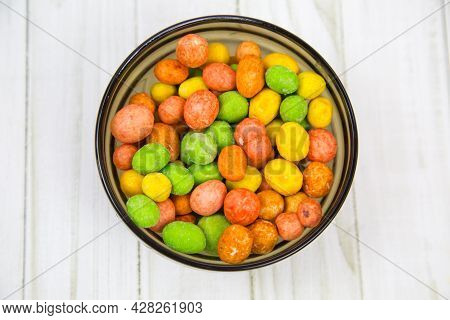 Peanuts In A Glaze Mix Of Bright Multicolored Flowers On A Black Round Plate With A Wooden Table Bac