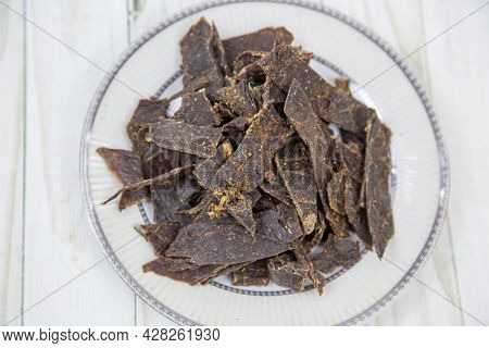 Deer Meat (lat. Cervidae) Dried, Cut Into Strips On A Round Plate With A Wooden Table Background. Fo