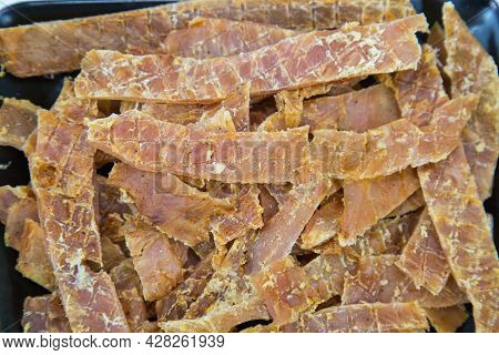 Turkey Meat (lat. Meleagris Gallopavo) Dried Sliced Into Strips On A Black Rectangular Plate With A