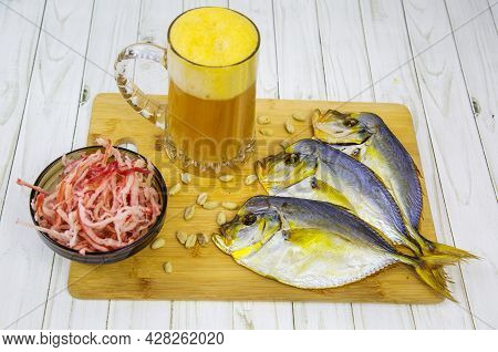 A Mug Of Beer With Foam, Dried Vomer Fish And Squid Shavings In A Round Black Plate On A Wooden Boar
