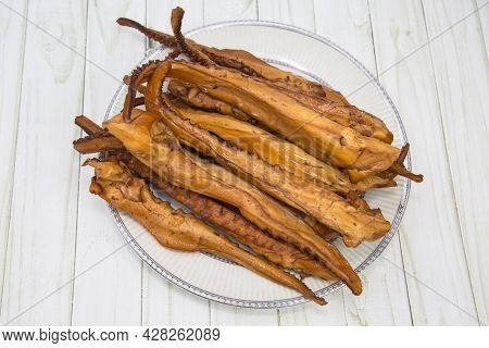 Octopus Tentacles (latin Octopoda) Are Brown On A Round Plate With A Wooden Table Background. Food I