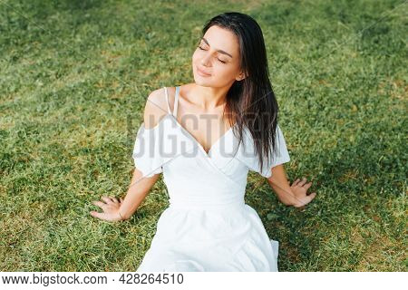 Charming Young Brunette Woman In White Light Dress Having A Rest With Closed Eyes On Green Grass Law